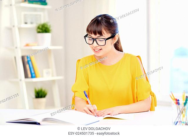 people, education, high school and learning concept - happy asian young woman student in glasses with book and notepad writing at home