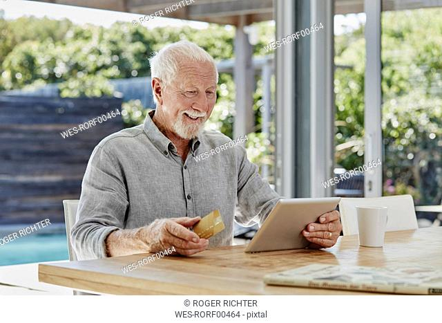 Senior man sitting on terrace, doing online payment with credit card