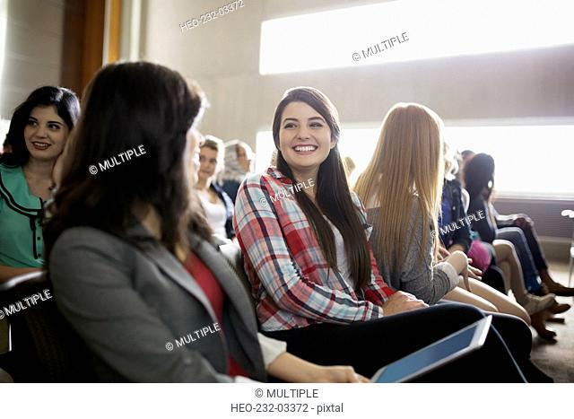 Smiling students talking in auditorium audience