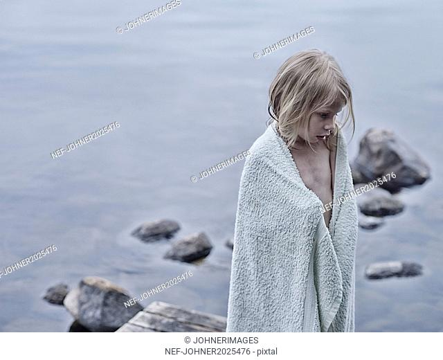 Girl wrapped in towel at water