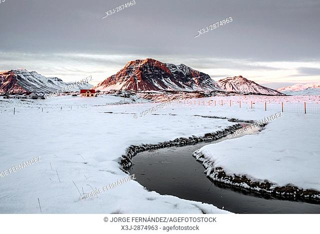 Icelandic landscape in which we can see a bunch of houses and the red light of the sun setting over the mountains in the background and a river in the...