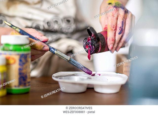 Female painter mixing color, color palette