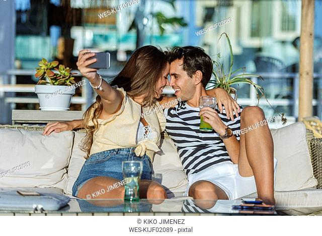 Happy affectionate young couple taking a selfie on the terrace of a bar