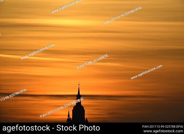 13 November 2020, Mecklenburg-Western Pomerania, Stralsund: Orange is the sky at sunset over the Hanseatic City of Stralsund and the top of St