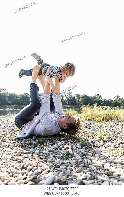 Father and son having fun at the riverside, playing aeroplane