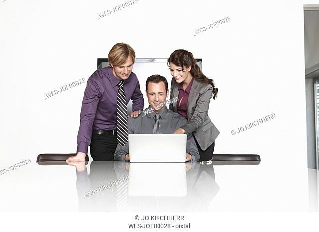 Germany, Cologne, Three business people in office using laptop