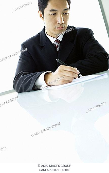 Businessman holding pen, writing