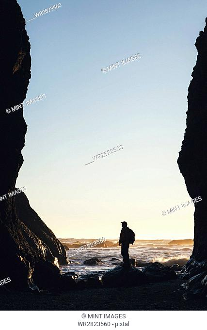 Silhouette of man standing between tall cliffs at dusk, the Pacific Ocean in the distance, Olympic National Park, Washington, USA