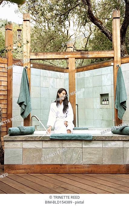 Hispanic woman preparing outdoor bath in spa