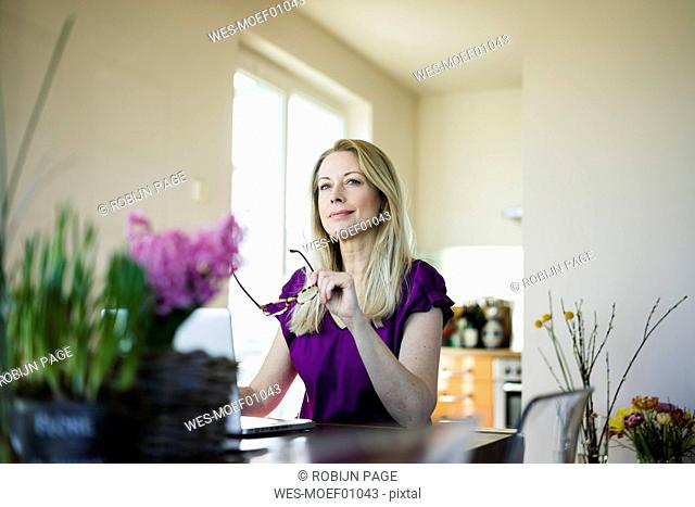 Portrait of businesswoman sitting at table using laptop at home