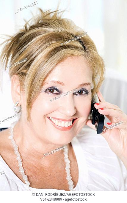 Senior woman talking on the phone and smiling at camera