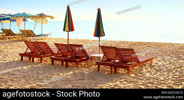 Group of wooden sunbeds on beach