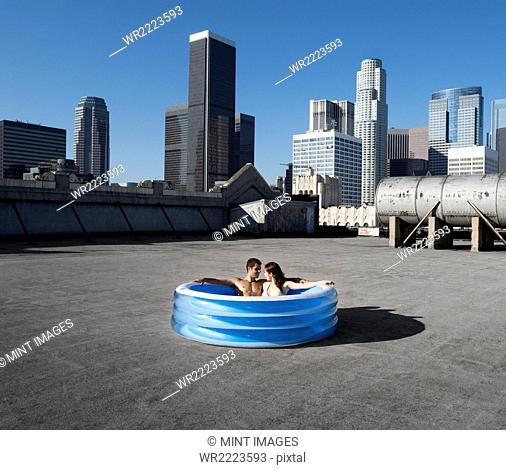 A couple, a man and woman sitting in a small inflatable water pool on a city rooftop, cooling down