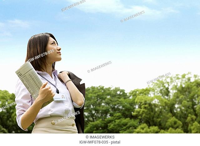 Japan, Osaka Prefecture, Businesswoman holding newspaper, looking up