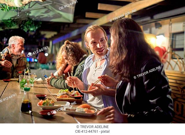 Couple eating, enjoying sushi on patio at night