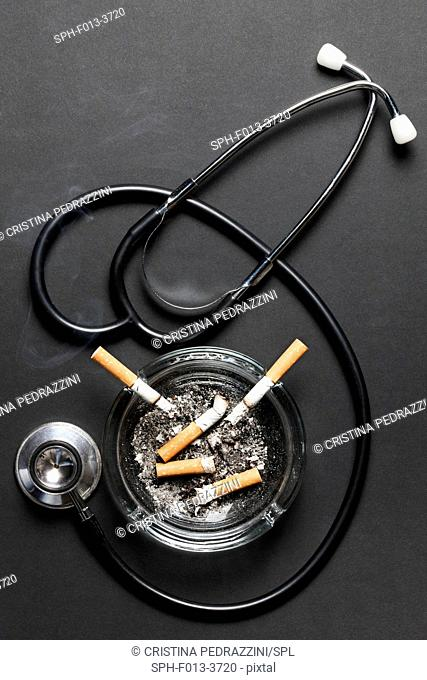 Cigarettes in ash tray with stethoscope