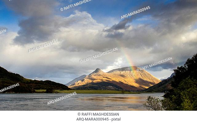 Scenic View Of A Lake And A Rainbow Cutting Through The Partly Cloudy Sky