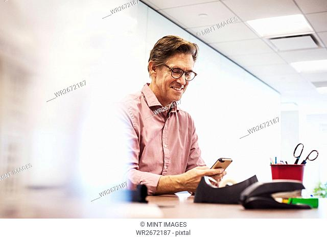A man sitting in a classroom at a table and looking down at a cellphone