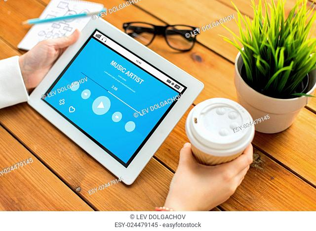 business, multimedia, technology, people and advertisement concept - close up of woman with music player on tablet pc computer screen and coffee cup on wooden...