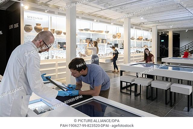 """24 June 2019, Baden-Wuerttemberg, Karlsruhe: Alexander Wolny (l), chief explainer of the exhibition """"""""Archäologie in Baden - Expothek¹ """""""" presents an object to..."""