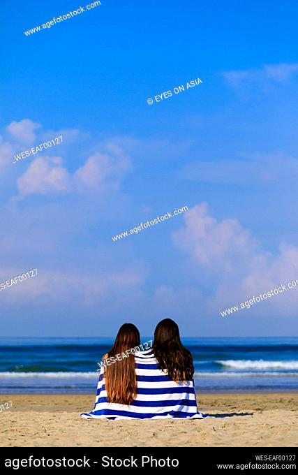 Women wrapped in towel sitting at beach during sunny day