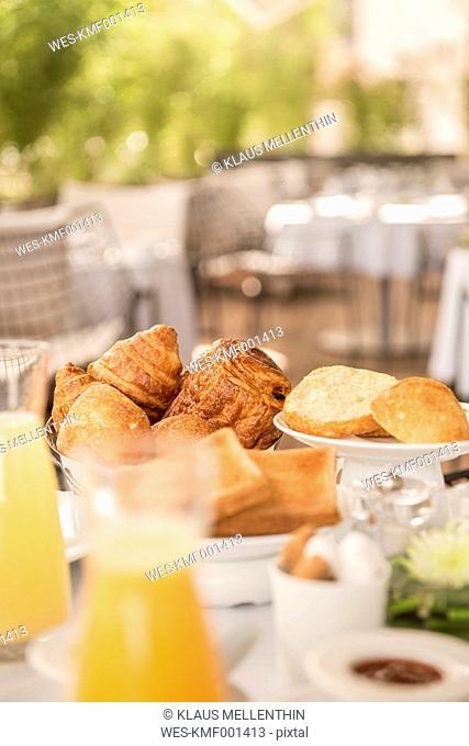 Germany, Breakfast, Bread roll, Croissants and juice on terrace