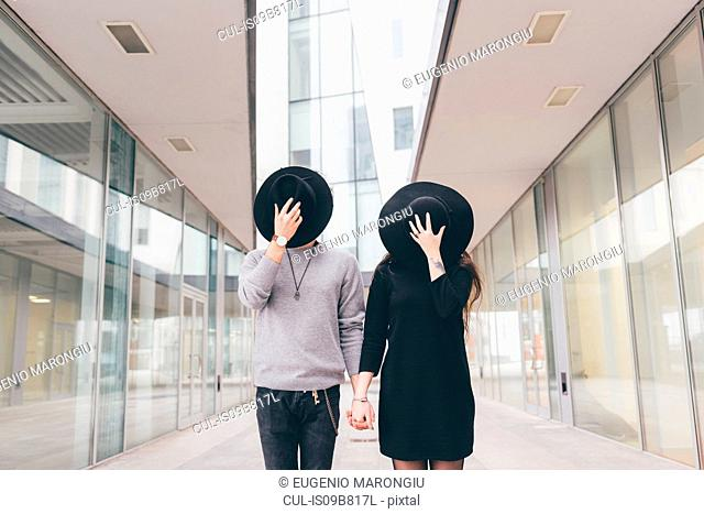 Portrait of young couple in urban environment, holding hands, covering faces with hats