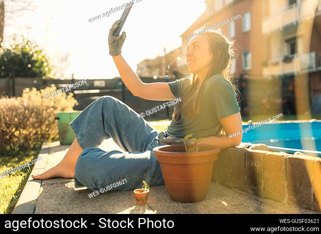 Young woman in garden with seedling in flowerpot taking a selfie