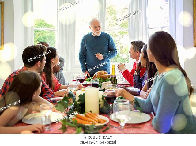 Grandfather preparing to carve Christmas turkey at dinner table