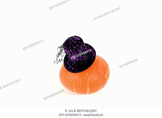 isolated pumpkin wearing a black witch hat on a white background..Minimal color still life photography
