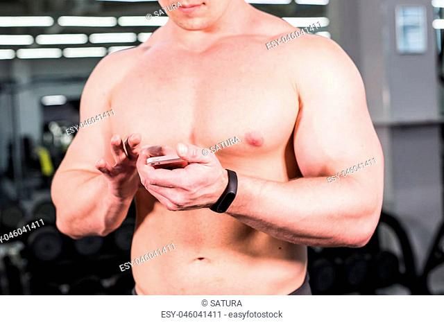 muscular sports man use activity tracker in gym