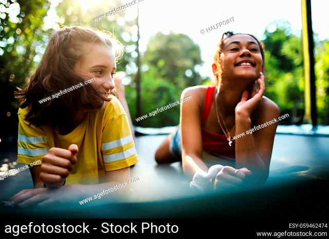 Front view of cheerful young teenager girls friends outdoors in garden, laughing