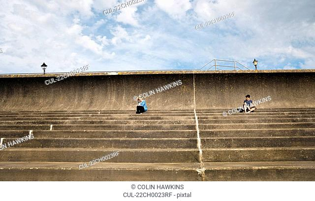 Man and woman sitting apart on steps