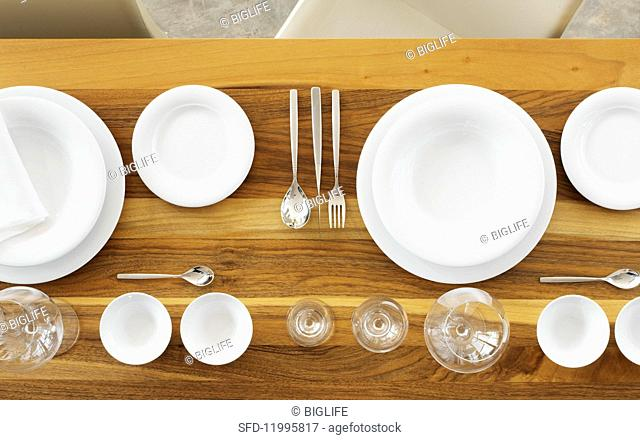 White plates, silver cutlery, glasses and bowls ok a wooden table (seen from above)