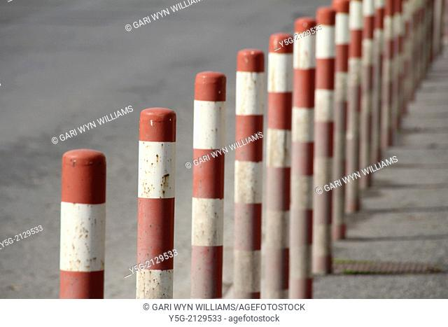 row of red white posts in street in rome italy