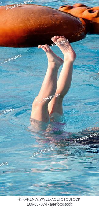 Legs of 10-year-old girl doing handstand in pool, all but legs under water, in sunshine, floating hippo water toy in background