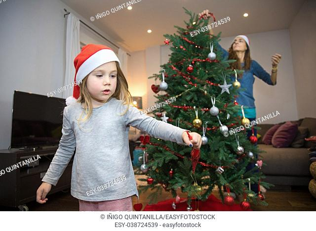 four years blonde cute girl with red Santa Claus hat and mother decorating Christmas tree at home
