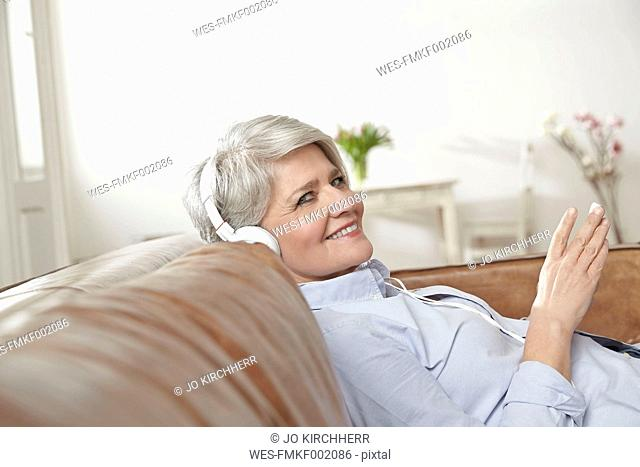 Mature woman sitting on couch listening to music