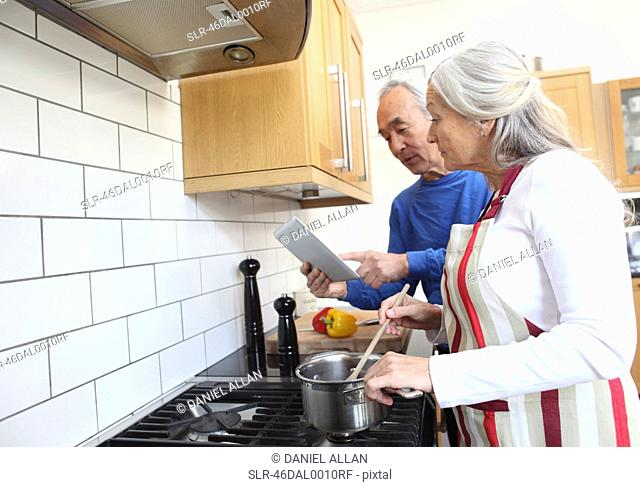 Older couple cooking together in kitchen
