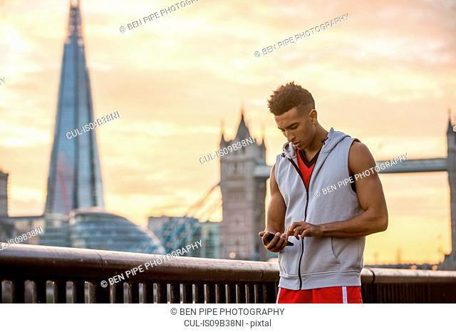 Man using mobile phone by riverside, Tower Bridge and The Shard in background, Wapping, London, UK