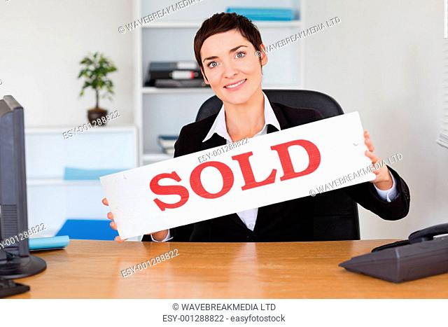 Happy real estate agent with a sold panel in her office