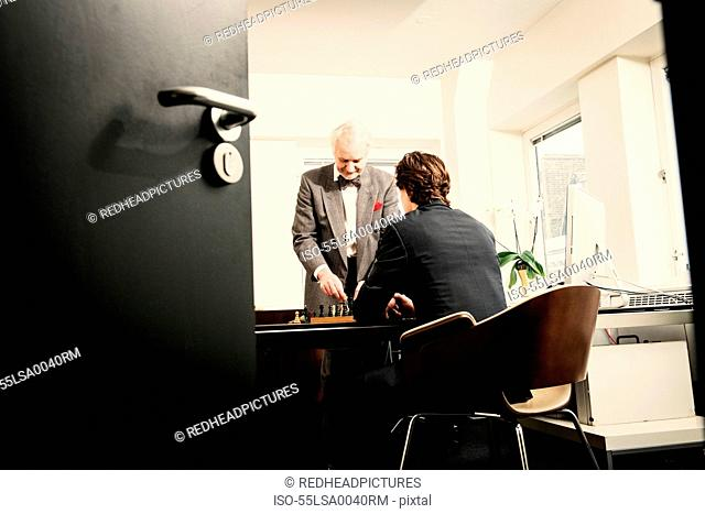 Two men playing chess in office