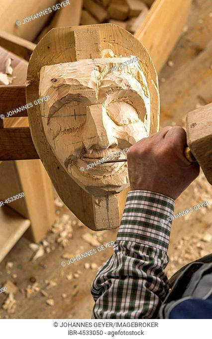 Carving the mouth of a wooden mask using wood carving tools, wooden mask carver, Bad Aussee, Styria, Austria