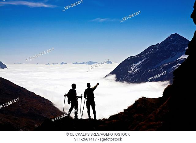 Two trekkers hike above the clouds, Engadina, Swiss alps, Switzerland