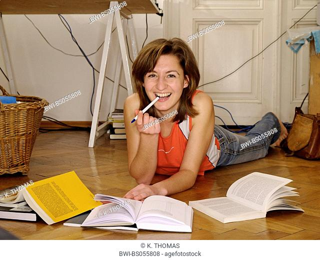 Young Woman / twen, lying on the floor in the midst of books laughing