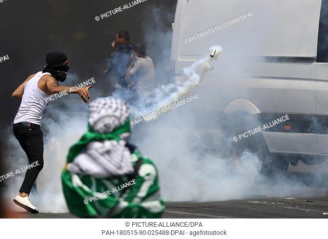 dpatop - A Palestinian protester throws back a tear gas canister fired by Israeli Security Forces during clashes following a protest against the US embassy move...