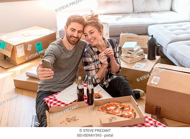 Moving house: Young couple taking self portrait with smartphone, in new home, surrounded by boxes
