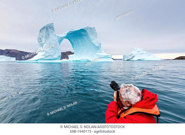 Photographer with huge icebergs in Scoresbysund, Northeast Greenland