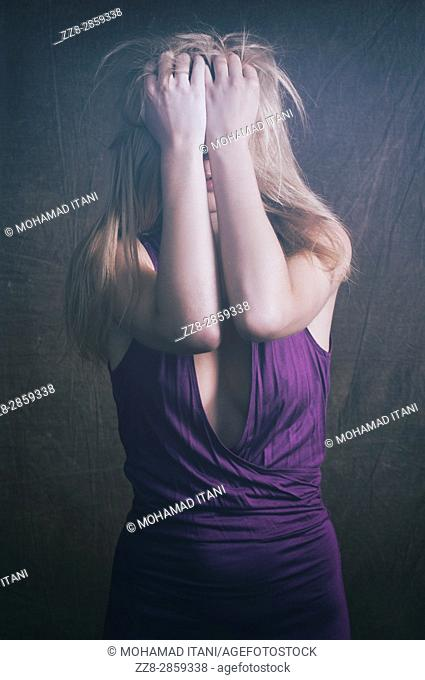 Frustrated young blond woman head in hands