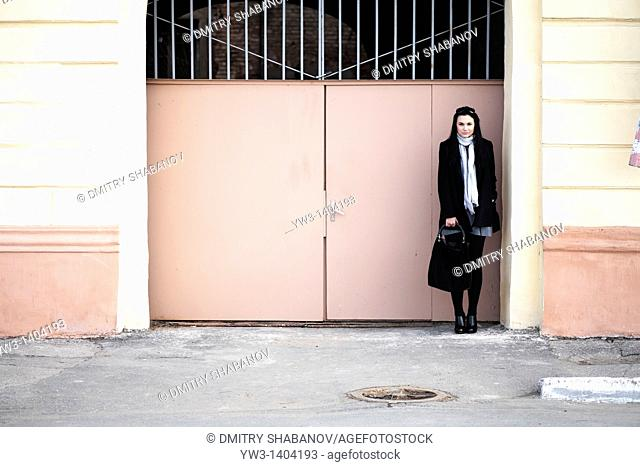 portrait of a beautiful 20-25 years women outdoors in the spring near metal gates